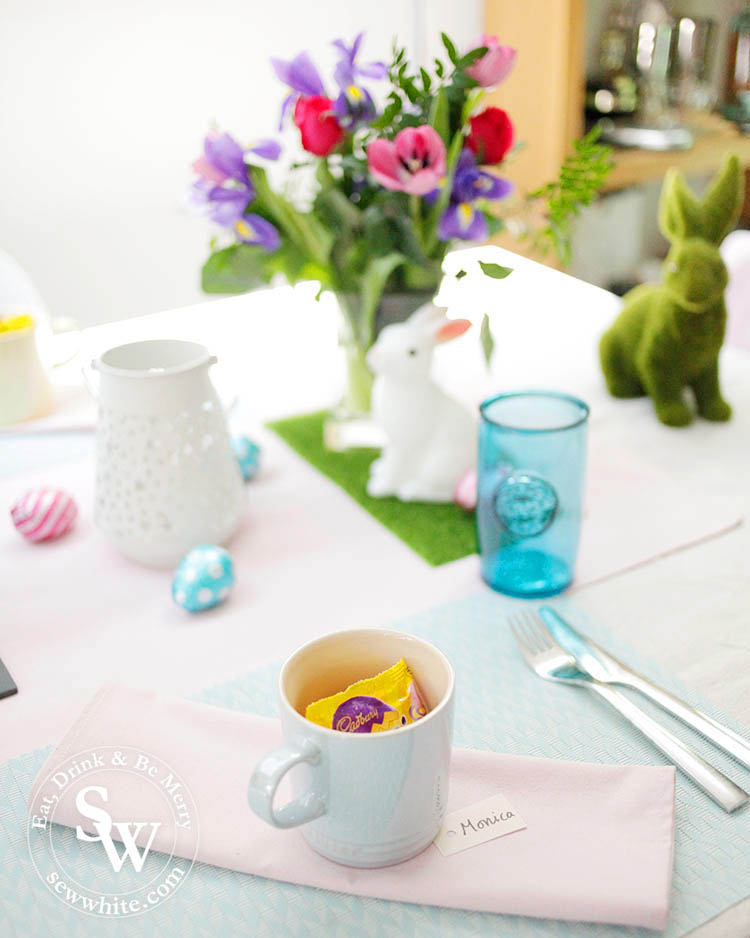 pastel Easter table with pink napkins and settings of cups with mini eggs.
