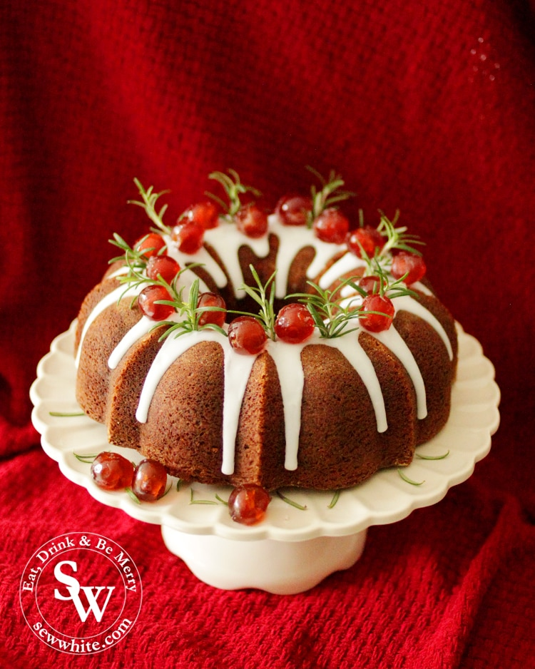 Black Forest Christmas Bundt Cake on a white cake stand decorated with rosemary and red galce cherries.