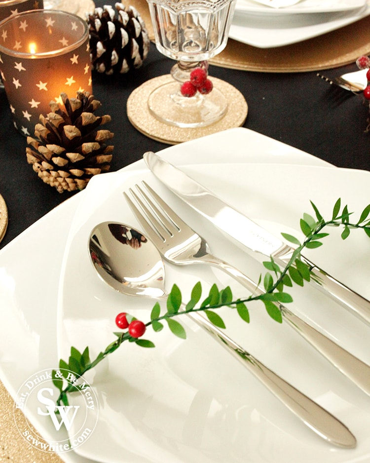 close up the Black Gold and Red Christmas Table setting with cutlery from Viners. Plates from marks and spencers, glasses from Sainsburys.