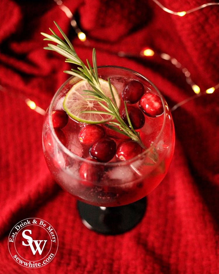 Beautiful red cocktail with a sprig of rosemary, fresh cranberries and a slice of lemon in the Christmas Cranberry Gin Cocktail
