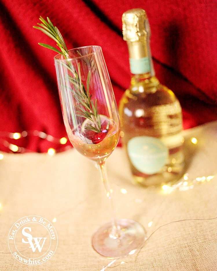 A champagne glass filled with raspberry liqueur, rosemary sprig, fresh cranberries and a slice of lemon for the Raspberry Rosemary Fizz