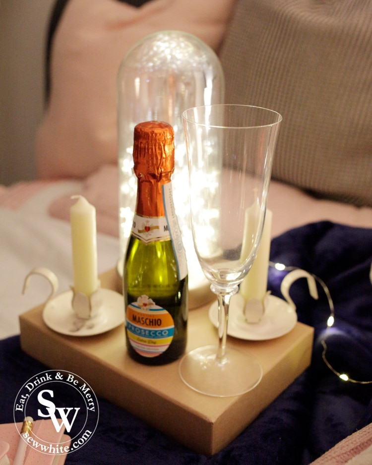 mini bottle of prosecco and candles ready for a pamper night in with Keep the Faith London