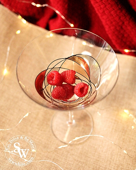 raspberries in the bottom of a glass for the Rum and Raspberry Cocktail