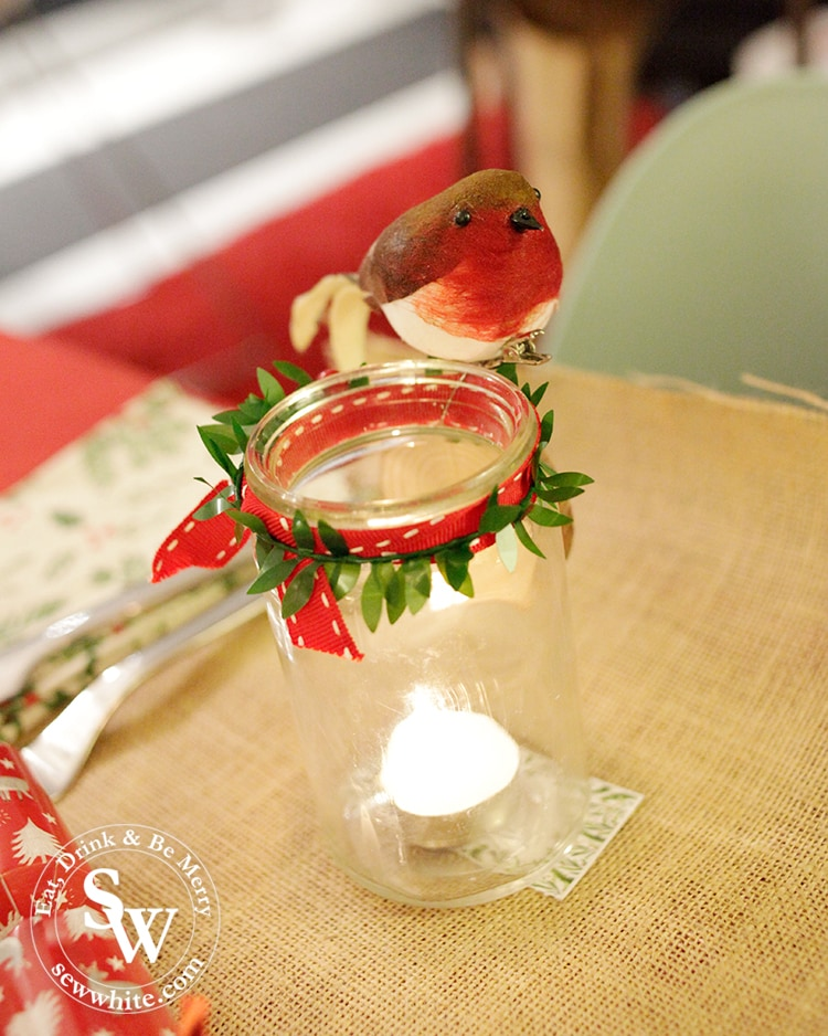 glass jar with red ribbon and a robin on for the Christmas table.