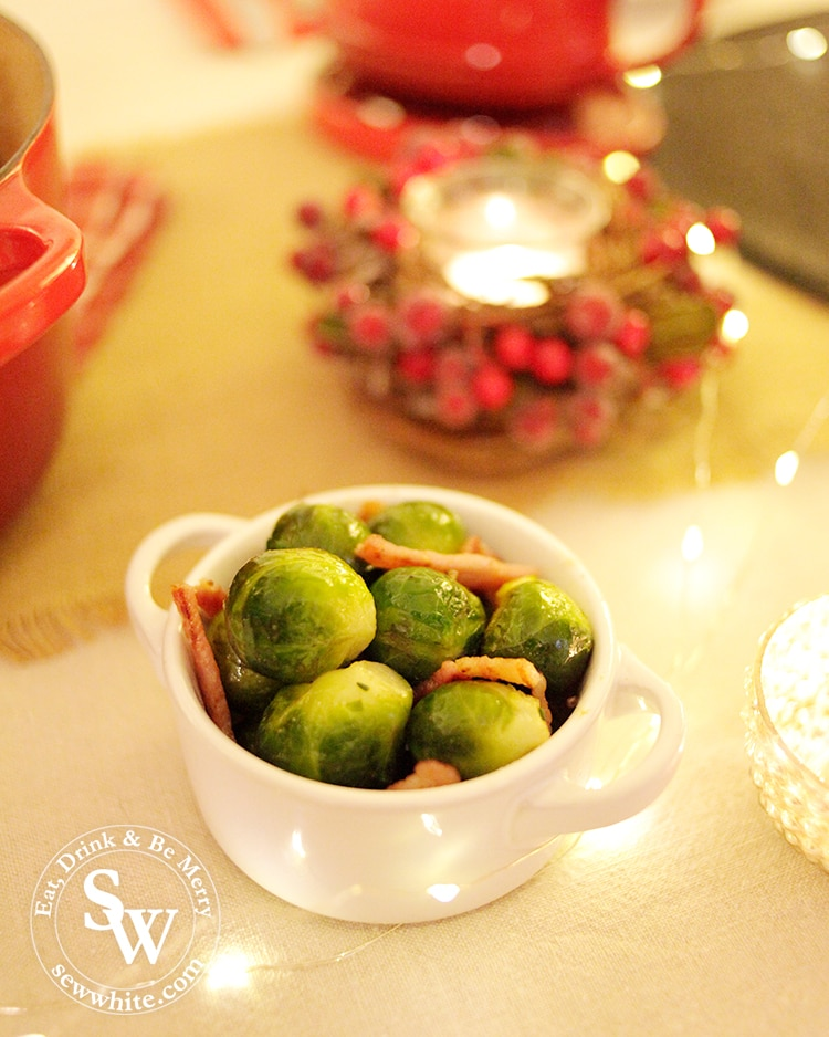Brussels Sprouts cooked with bacon and salt in the Le Creuset petite casserole on the Christmas table surrounded by candles.