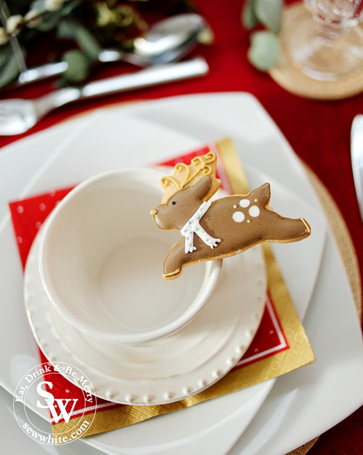 Biscuiteers reindeer biscuit on the place setting for the Red Gold and Nature Christmas Table