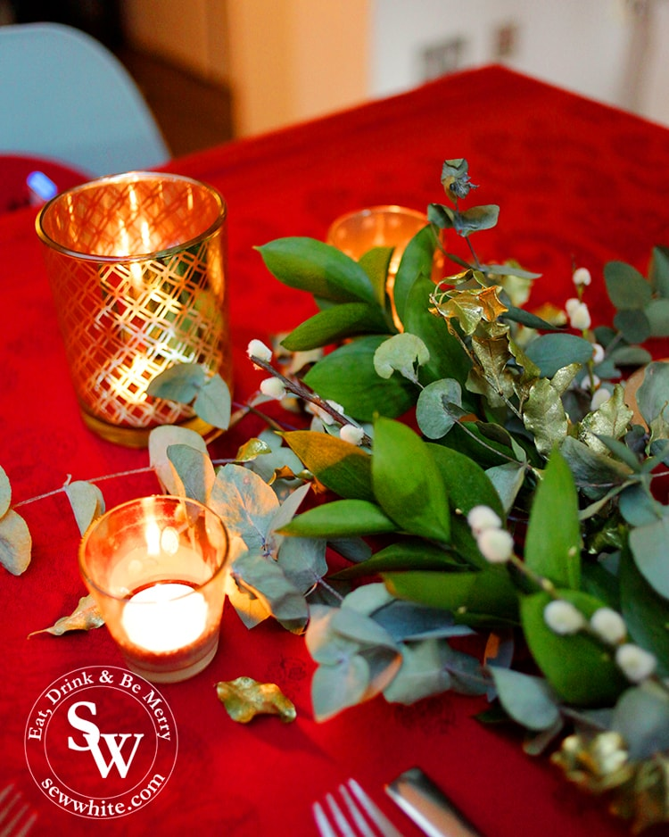 Christmas table with red table cloth and fresh greenery studded with golden candles.
