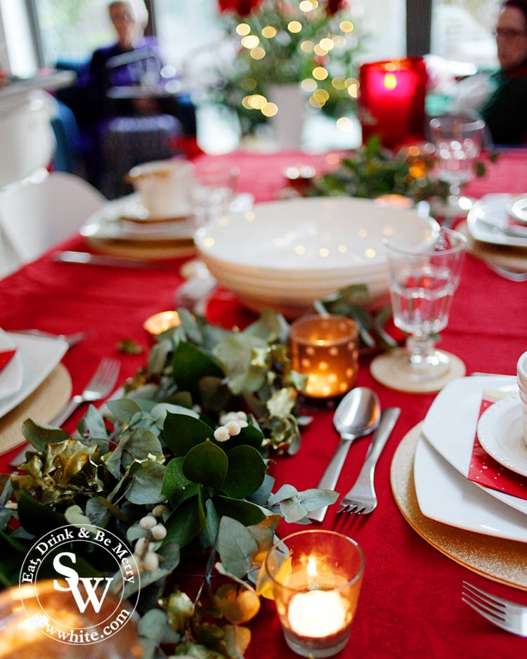 Red Gold and Nature Christmas Table using real foliage and candles on a red table cloth.