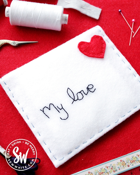 felt envelope with embroidered name on and red heart for a stamp.