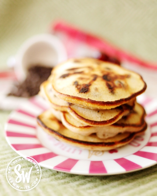 golden stack of pancakes on a pink stripy plate made with chocolate and cherries.