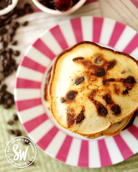 Close up beautiful golden brown Chocolate Cherry Pancakes on a pink stripy plate.