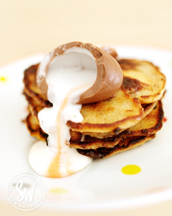 A Cadburys Creme Egg oozing over a stack of golden Creme Egg Pancakes