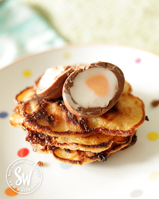 Creme Egg Pancakes, topped with an open creme eggoozing over the pancakes on a polka dot plate