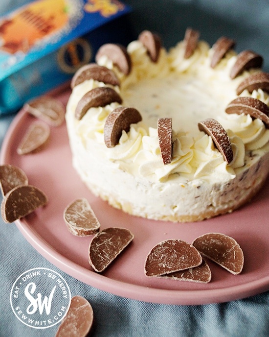 The chocolate orange cheesecake with Terry's chocolate orange pieces on top ready to serve on a pink plate.