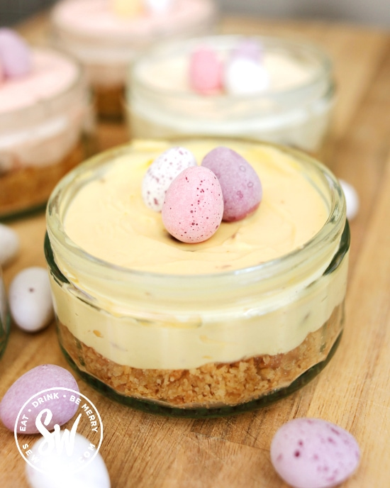 pastel yellow mini egg cheesecake in a glass jar.