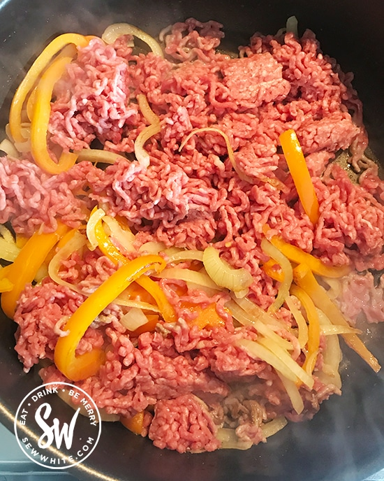 Stirring in the beef mince into the onions and peppers.