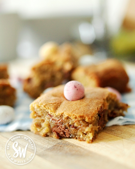 Mini Egg Cookie Traybake slice with soft middle and chopped up mini eggs inside.