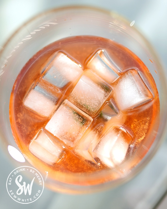 Golden orange Aperol cocktail with apple juice and bright white ice cubes ready to be topped up with cloudy apple juice