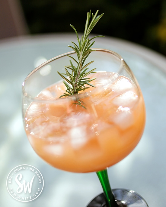 orange Aperol apple cocktail served with a sprig of rosemary on a sunny day.