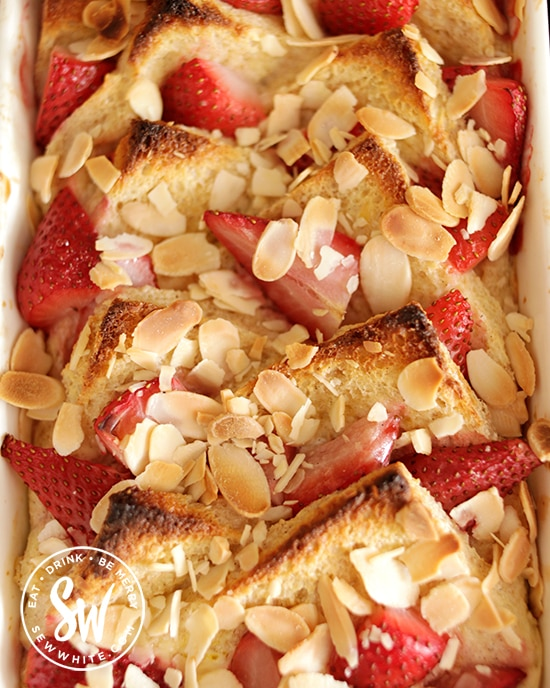 Golden brown toast almonds on a strawberry bread and butter pudding fresh from the oven
