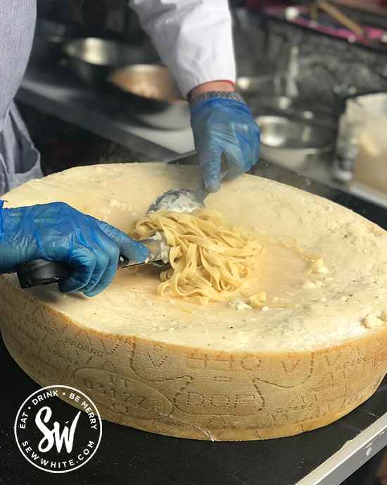 cooked pasta being rolled in a wheel of cheese at the love wimbledon market.