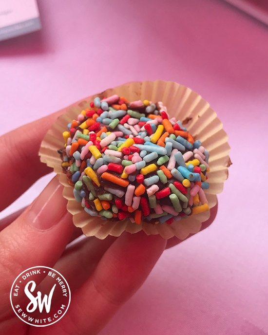 Brightly coloured sprinkles on chocolate truffles