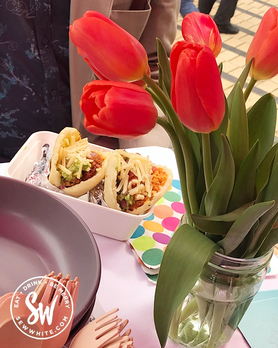 Street food at the Love Wimbledon market. A table with red tulips.
