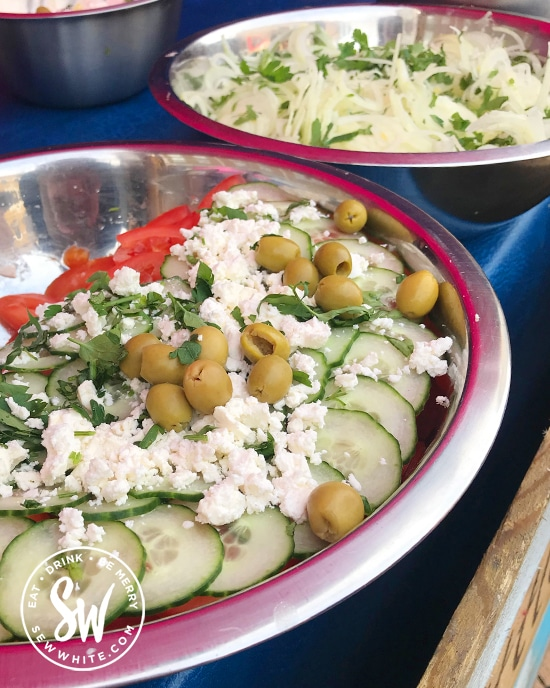 A big greek salad with olives and feta cheese.