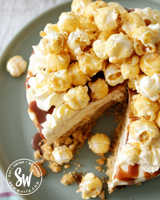 cheesecake with toffee sauce drizzled over and popcorn on top on a blue plate.