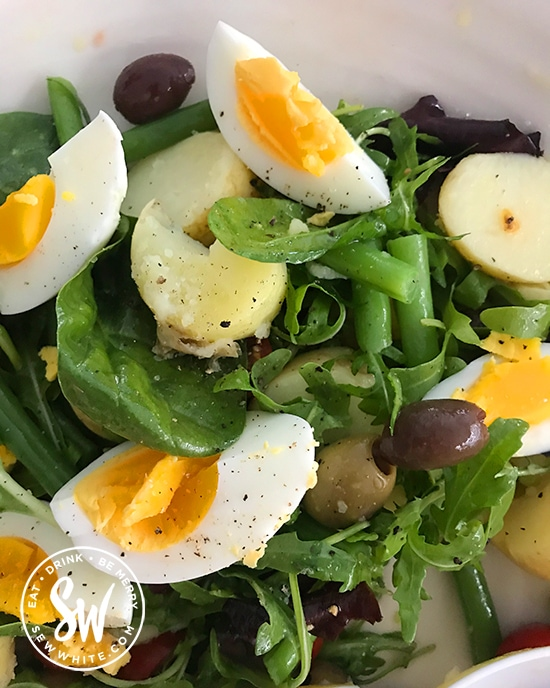 sliced boiled egg pieces sprinkled with pepper, with green beans and new potatoes on a bed of salad leaves in the easy egg salad