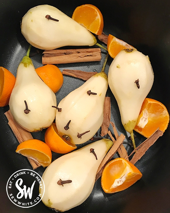 orange segments, cinnamon and cloves in a slow cooker with pears