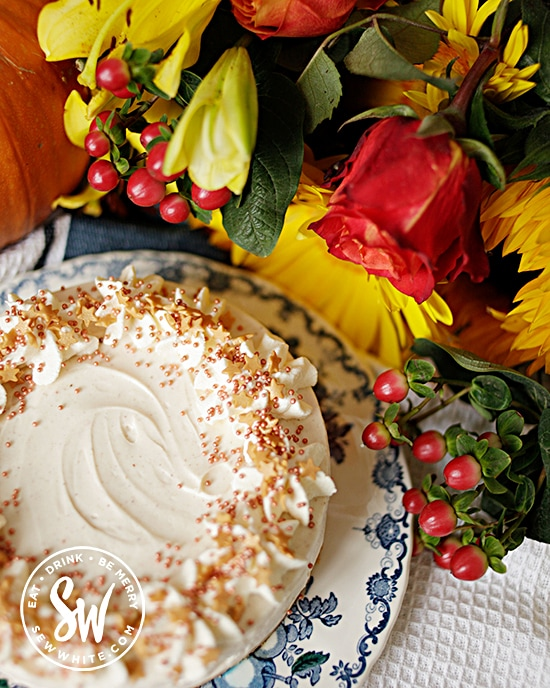 cheesecake with golden sprinkles on a blue and white plate surrounded by flowers and a pumpkin