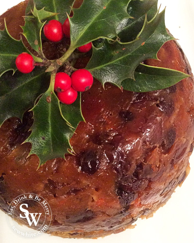 An English traditional Christmas pudding decorated with a sprig of holly.