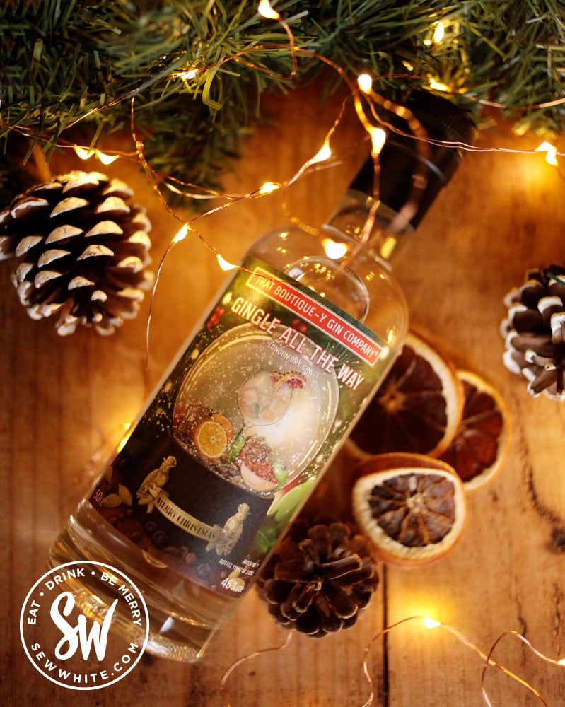 Gingle all the way Christmas gin bottle on a table surrounded by fairy lights and Christmas garland in the drink gift guide