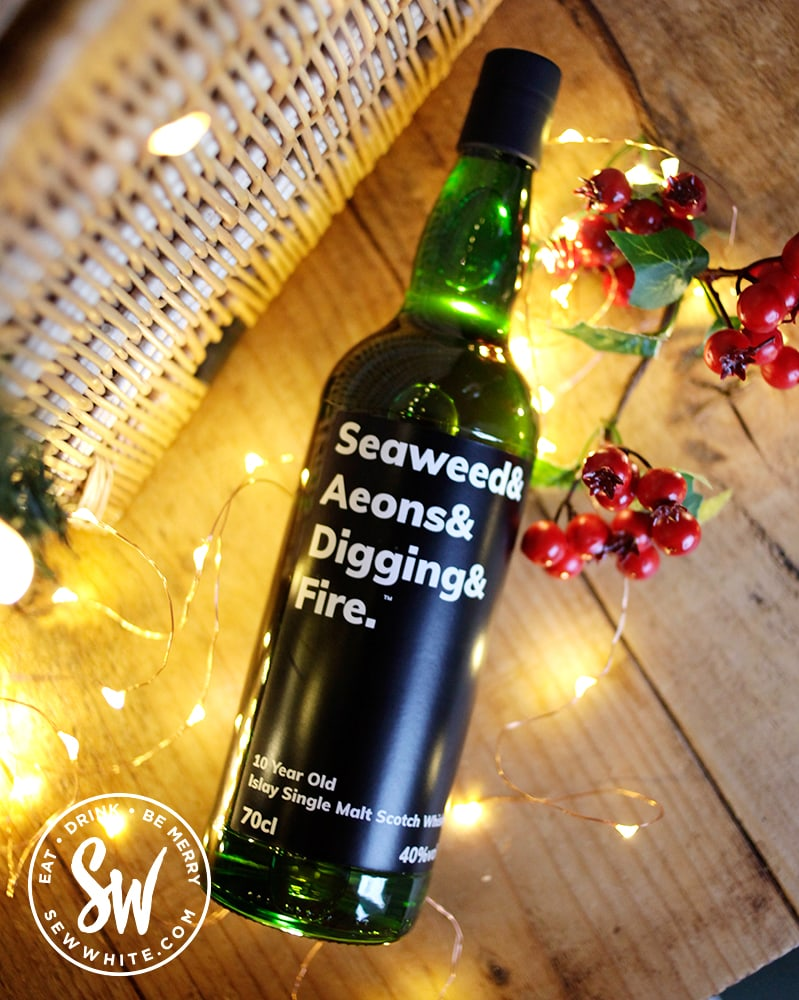 Seaweed & Aeons & Digging & Fire single malt bottle in the drink gift guide lying on a table with lights around it
