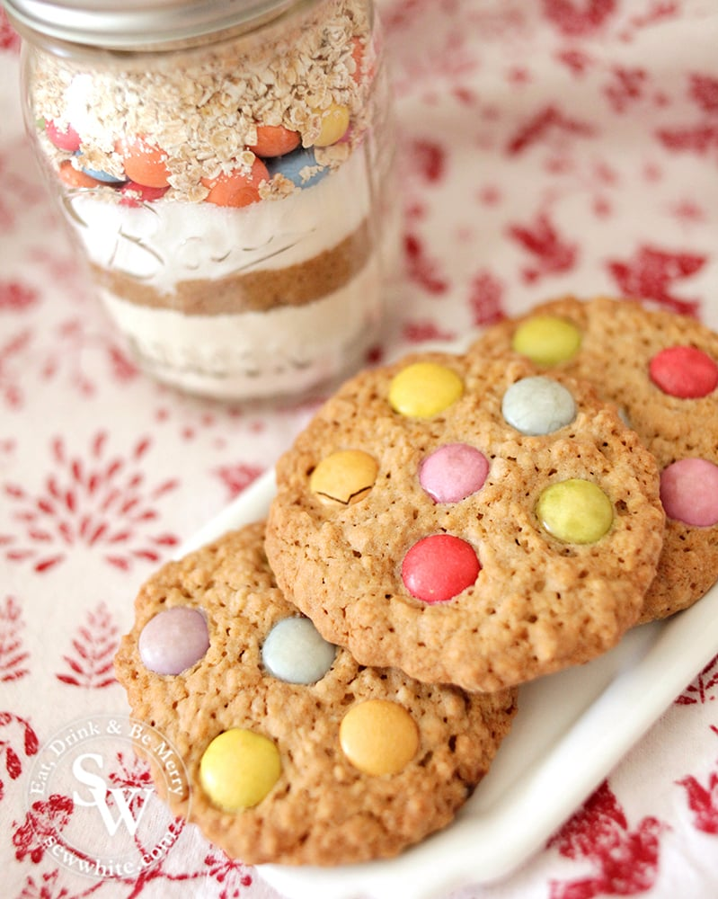 Cookie jar next to 3 finished cookies on a white plate