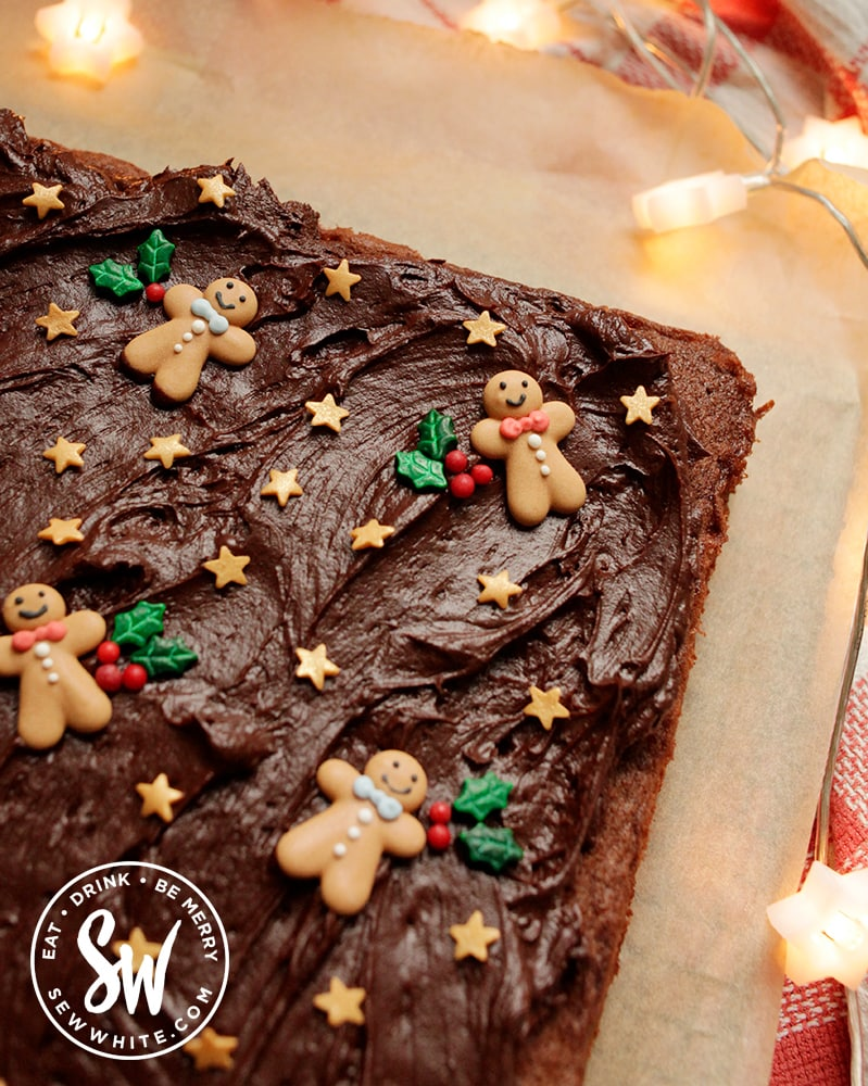 Christmas Chocolate traybake with a thick layer of chocolate cream cheese buttercream decorated with Christmas sprinkles
