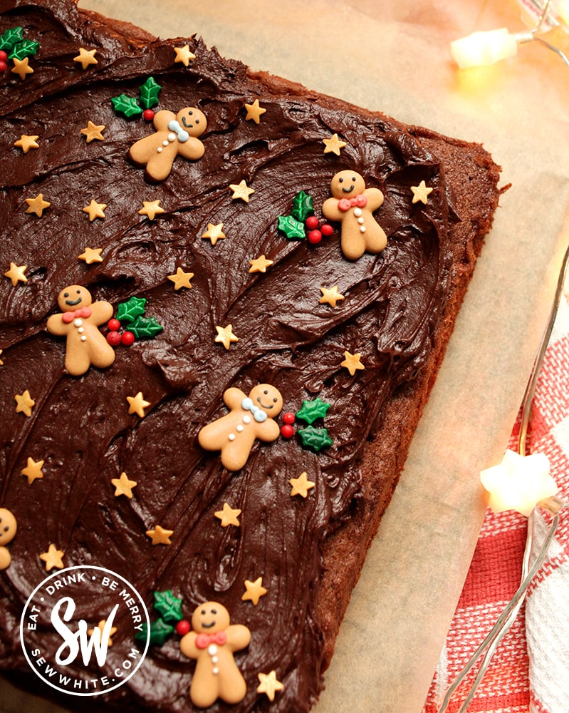 Chocolate traybake for Christmas on a sheet of greaseproof paper decorated with chocolate buttercream and sprinkles