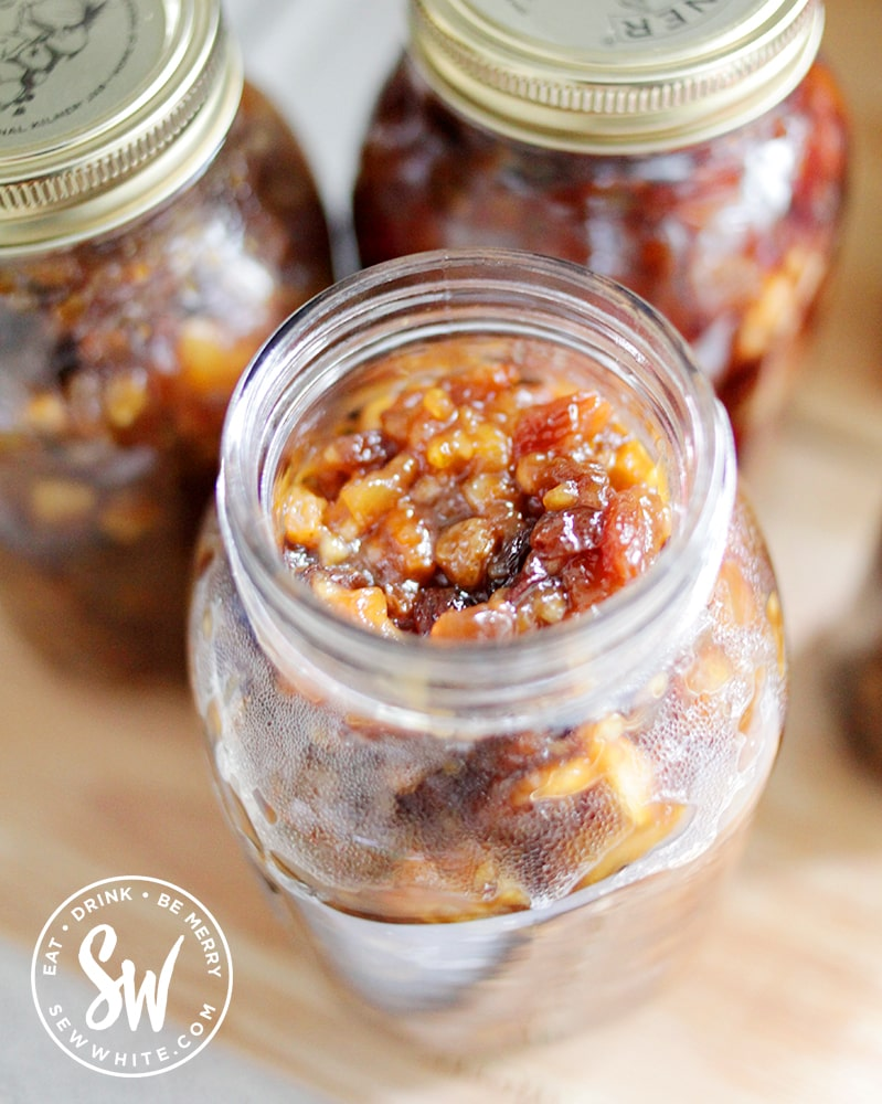 golden mixed fruit in the vegan mincemeat in a glass kilner jars after being cooked in the slow cooker