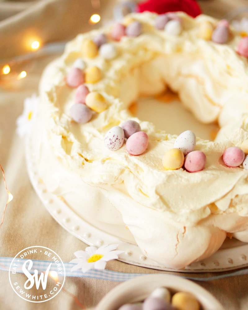 The finished Easter meringue served on a white plate, topped with cream and mini eggs