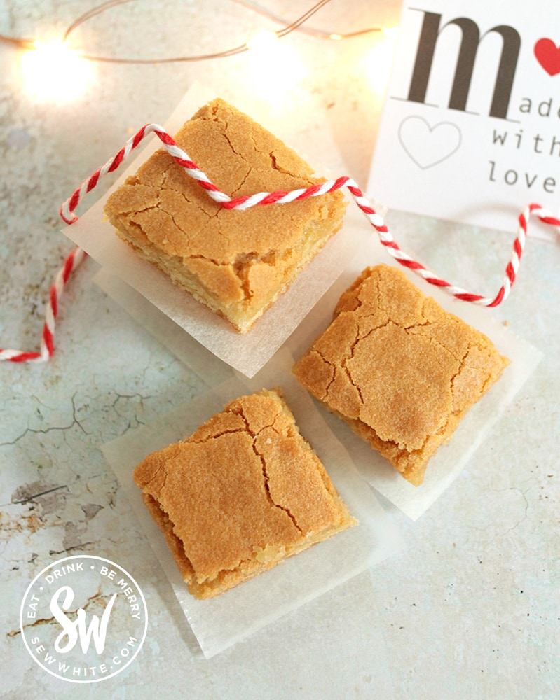 Golden brown easy Blondies sliced up and being wrapped in greaseproof paper and red string