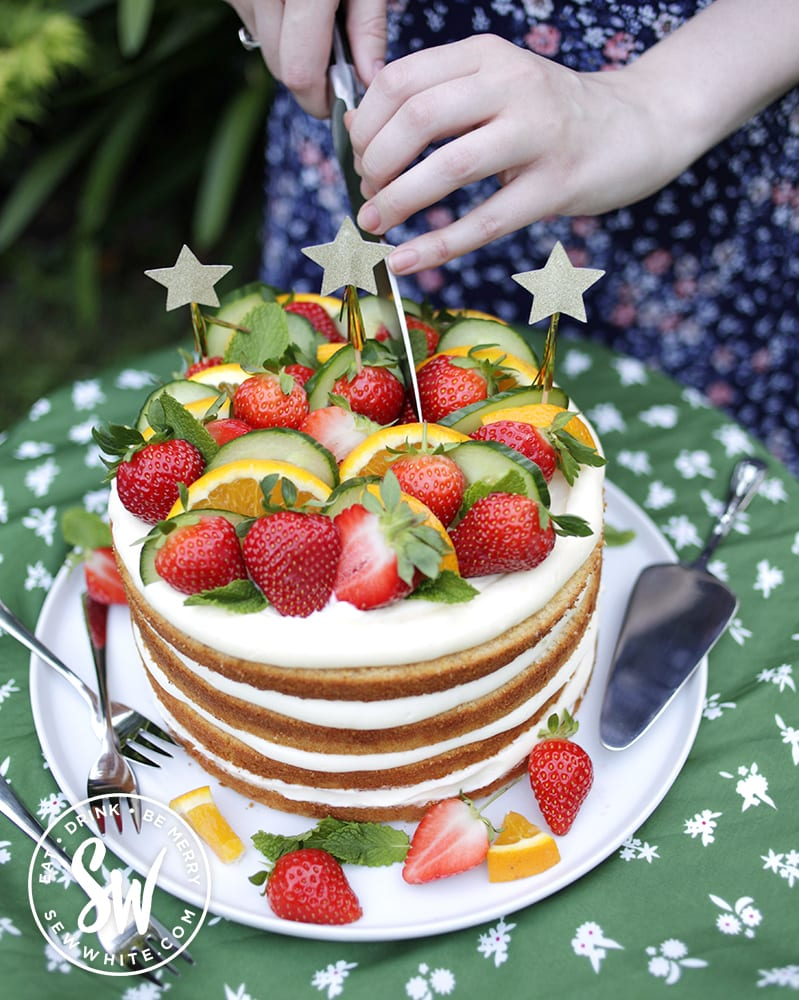Pimm's layer cake being cut into with fhres fruit on top of the layers