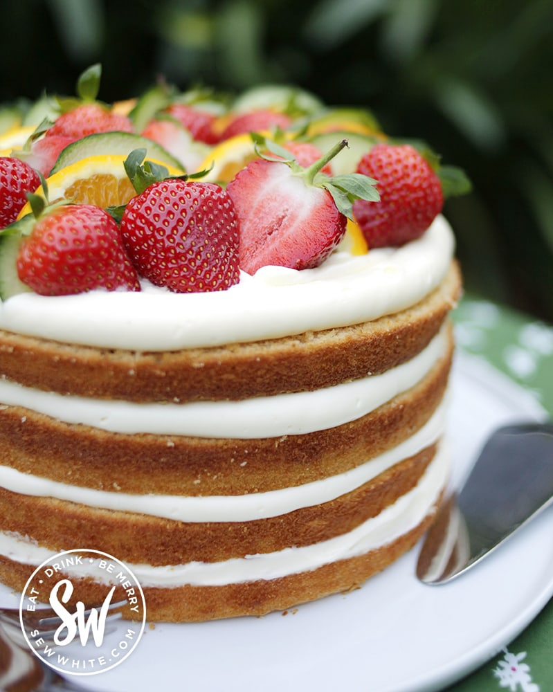 beautiful golden brown impressive cake with layers of buttercream and topped with pimm's fruit